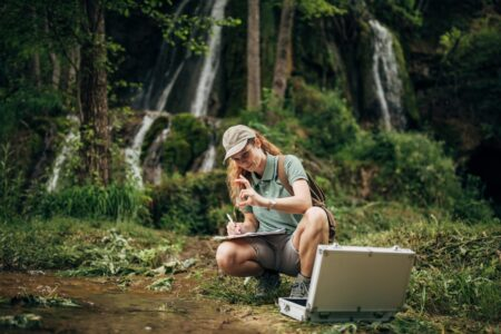 Woman sitting by river analyzing water sample.
