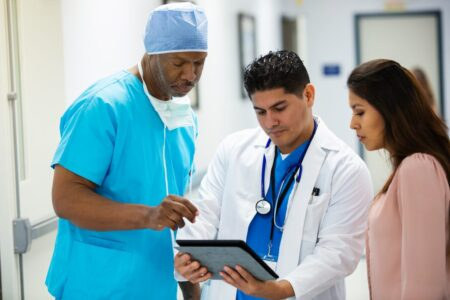 Three doctors discussing a patient's chart.