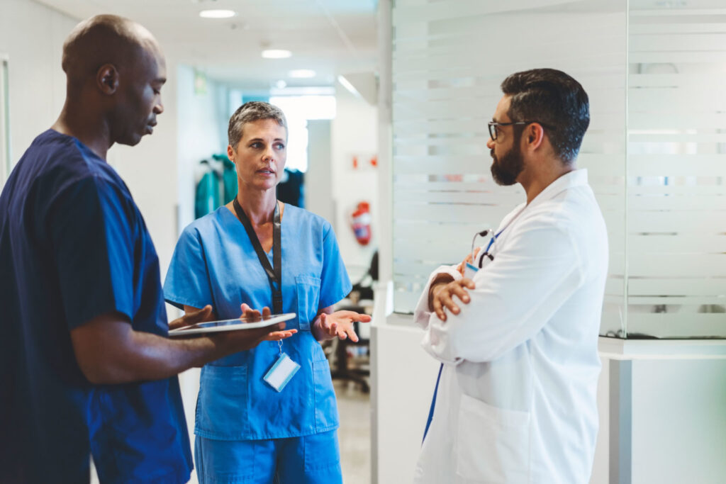 Healthcare workers conversing in a clinical setting