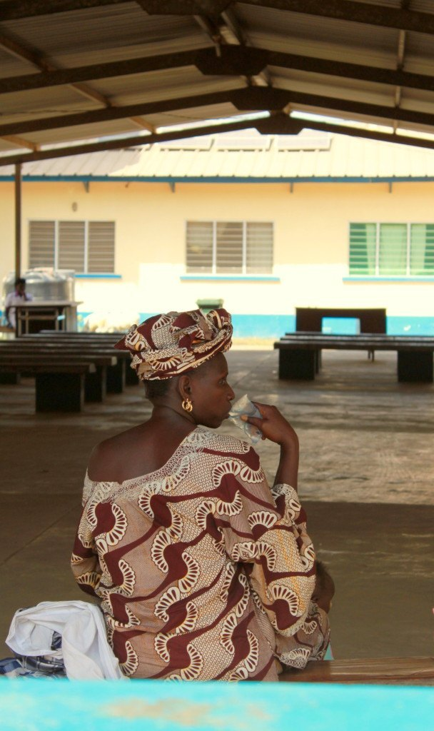 A woman outside the Fajikunda health center waits for her daughter who was in labor inside the facility