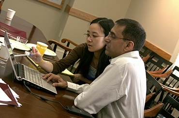 Two people looking at a computer screen together in conference room at Harvard Pop Center