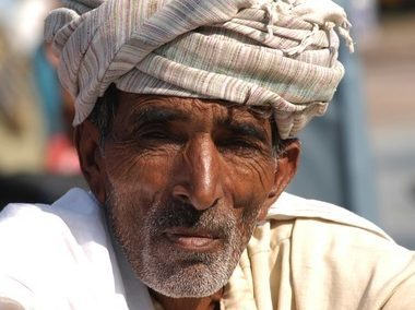 An older Indian man wearing a casual wrap around his head