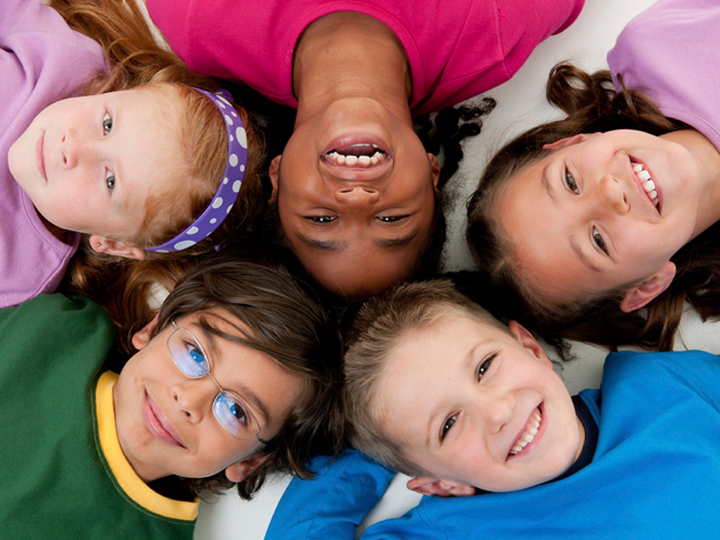 Group of multi-racial smiling children are lying on the floor, head to head