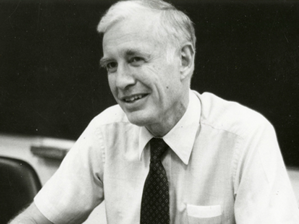 Black and white image of David Bell sitting behind a desk