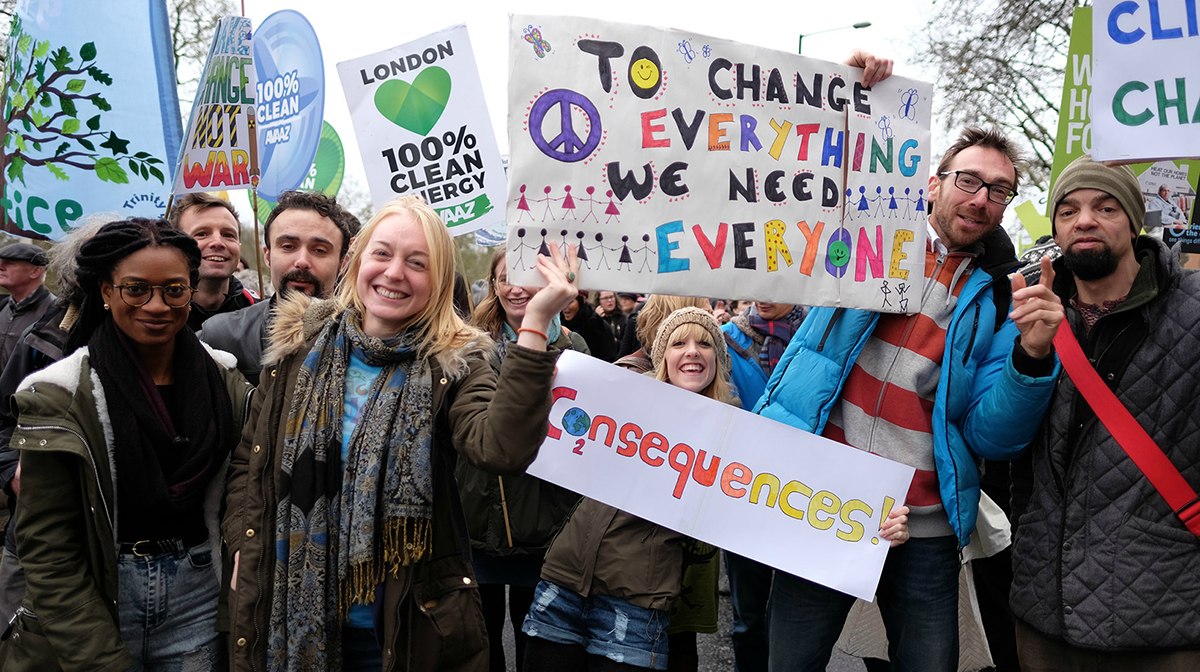 Men and women of different ethnicities with signs at a climate change rally