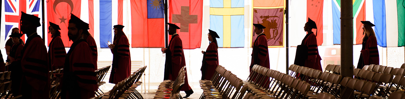 Graduates with flags in background