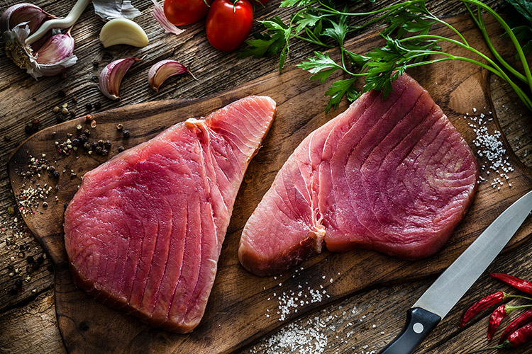 Raw tuna steak on a cutting board with garlic and tomatoes.