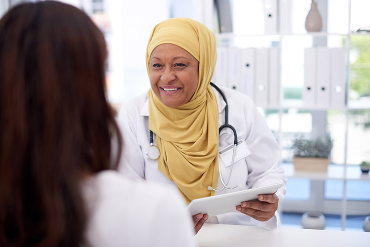 Female doctor in yellow hijab helps female patient.