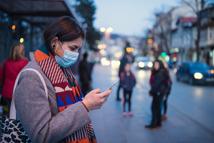 Young woman wearing a face mask looks at her phone at a bus stop.