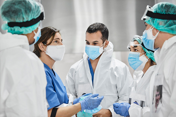 Health care team of five people wearing surgical masks and PPE talk together
