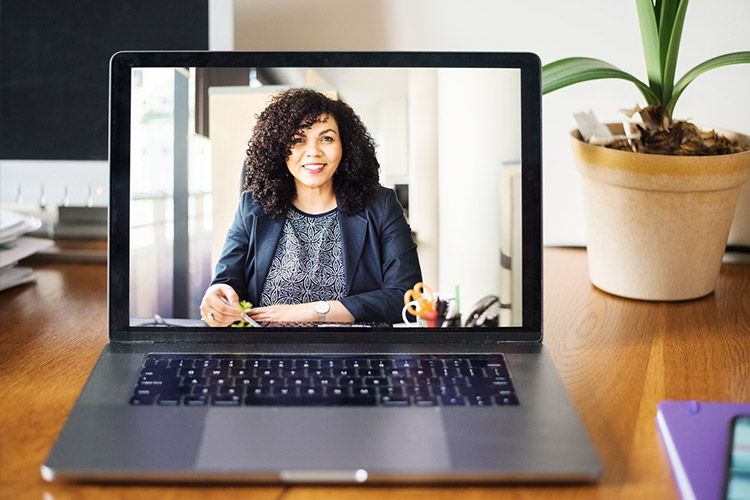 A laptop sits on a desk with an executive-level woman on the screen.