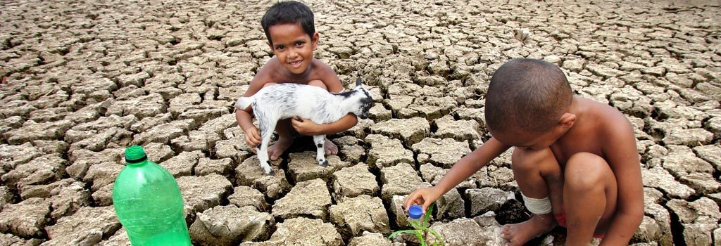 A child waters a plant in a dried-out field in India. © 2015 Dipayan Bhar, Courtesy of Photoshare
