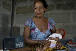 A mother with her infant in Tanzania listens to an HIV/AIDS radio program as part of the STRADCOM (Strategic Radio Communication for Development) project. Photo: ©2008 Robert Karam, Courtesy of Photoshare
