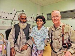 Michael McCarten with an Afghan girl and her father. The girl lost her lower left arm in a bus accident and suffered other serious injuries. McCarten's team performed several surgeries to ensure her survival.