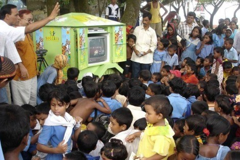 "In Bangladesh, where most don't have access to electricity, children watch Sesame Workshop's ""Sisimpur"" on a traveling rickshaw fitted with video equipment."