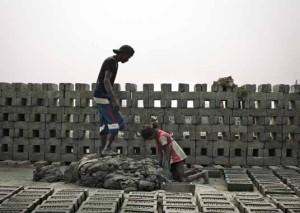 In the Indian state of West Bengal, a young man and a girl make clay for a brick kiln. Brickmaking is common employment for bonded laborers.