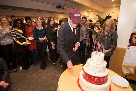 Dean Julio Frenk cuts the cake for eager partygoers.