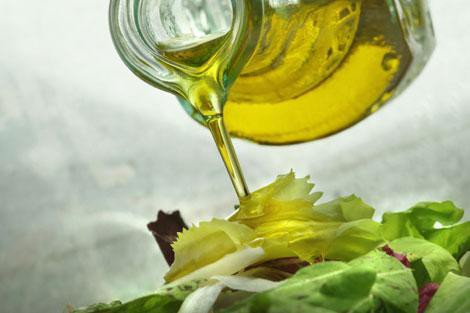 Olive oil pouring over a salad