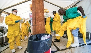 Medical staff working with Médecins Sans Frontiè res (MSF) don protective gear before entering an isolation area at the MSF Ebola treatment center in Kailahun, Sierra Leone, July 2014.