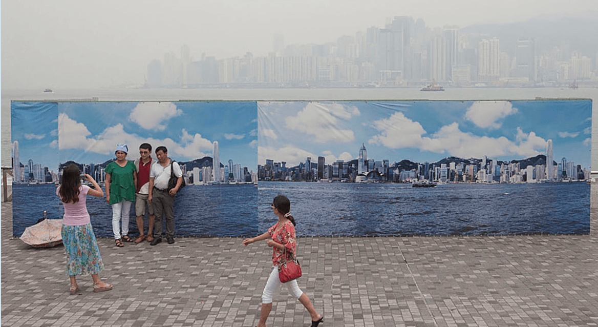 Tourists from mainland China pose for photos in front of an outdoor banner picturing what the Hong Kong skyline looks like on a clear day. Air pollution has reached record levels in Hong Kong n recent years, as it has in mainland China.