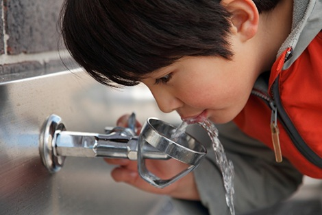 child drinking water from school water fountain