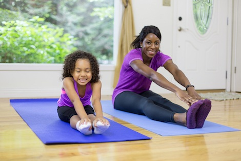 A mother and young daughter exercising together