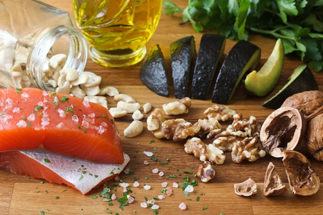 Salmon, avocado, nuts, and healthy oils on a board