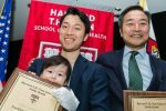 Father and baby with award