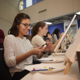 Female students painting on canvas
