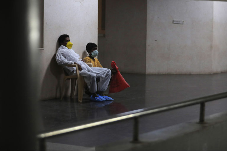 Patient and attendant wearing face masks in hospital waiting area.