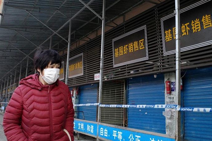 Person wearing mask walks by shuttered shops in Wuhan, China.