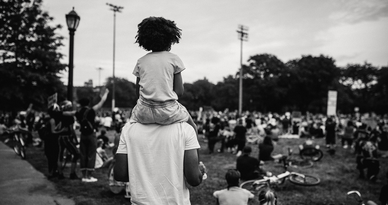 Black and white photo of young girl on her father's shoulders at a Black Lives Matter protest in Washington D.C.