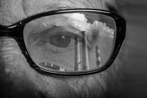 image of smoke stacks reflecting in a person's glasses