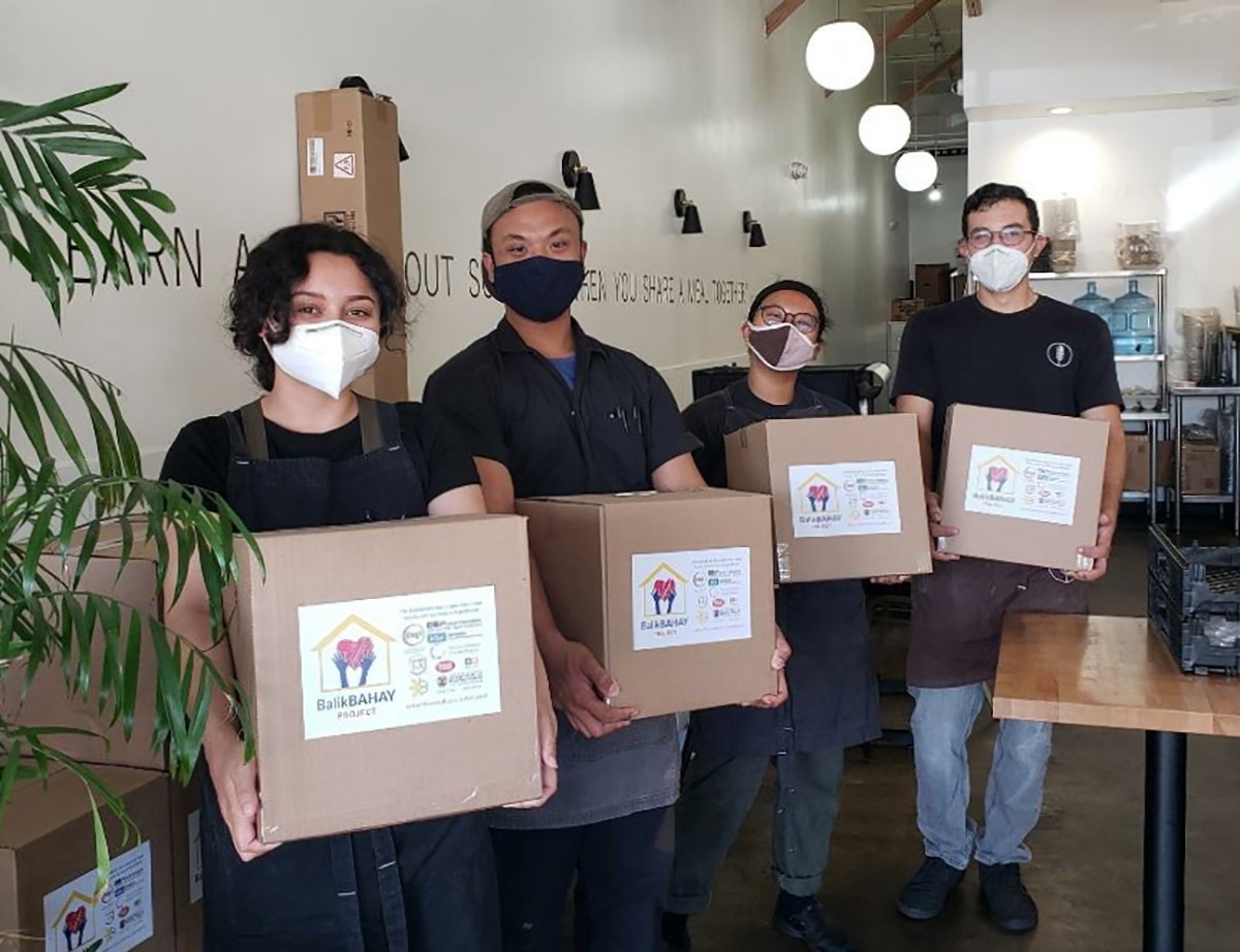 Photo of Antonio Moya and team posing with boxes of provisions