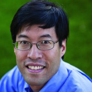 A man with dark hair, a blue shirt, and glasses smiles