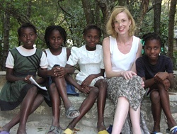 "Four young girls pose with Sue Goldie, a MacArthur ""genius"" award winner, in Haiti."