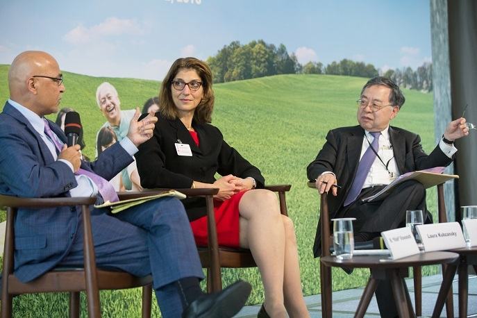 Vish Viswanath speaking on stage next to Laura Kubzansky and Ronnie Chan at Pathways to Happiness event in Hong Kong