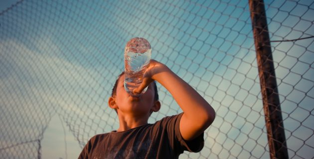 A boy drinks water on a hot day