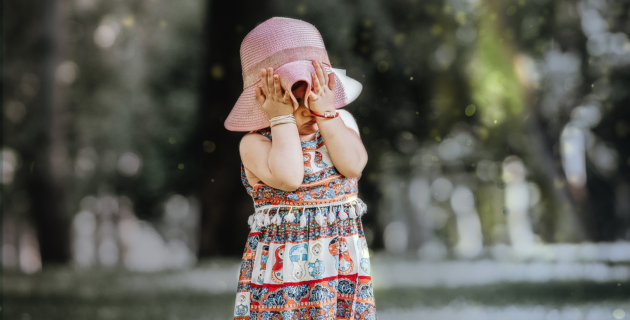 A young girl in a hat covers her face