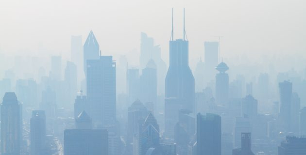 Photo of city high-rise buildings with a lot of smog in the air.