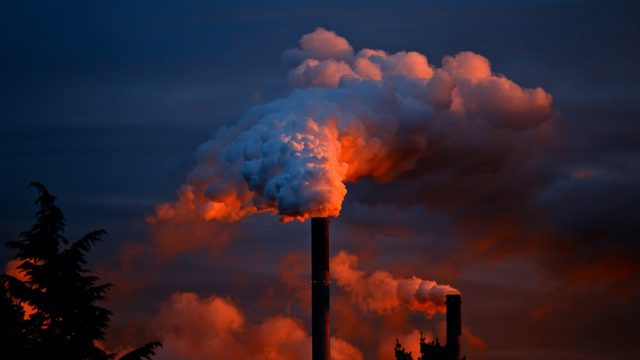 Air pollution and clouds of smoke coming out of a smoke stack during sunset.