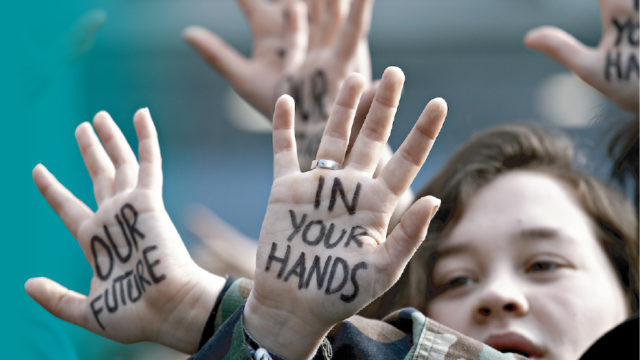 Youth hands protesting on banner of April 15th event on