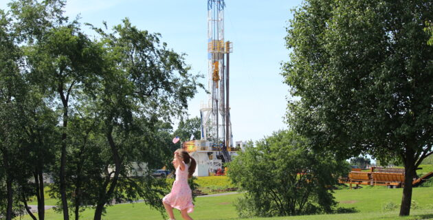 Girl plays near fracking site