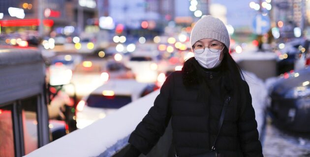 young woman wearing face mask in wintertime
