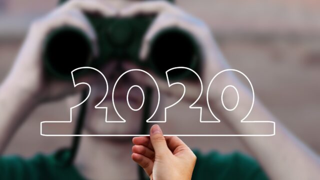 a person with binoculars looks at someone holding a 2020 sign