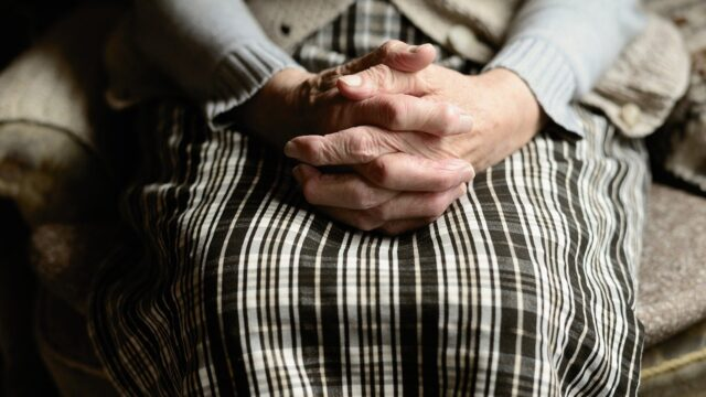 An elderly woman's hands folded in her lap