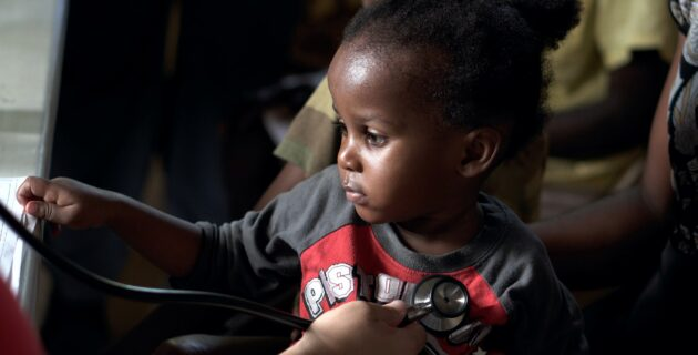A doctor uses a stethescope on a small boy