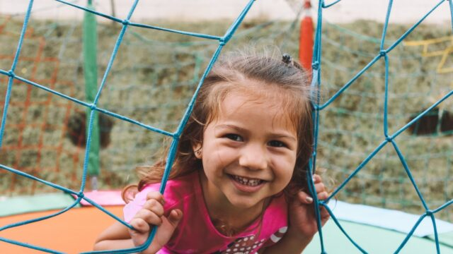 A young girl smiles on a playground