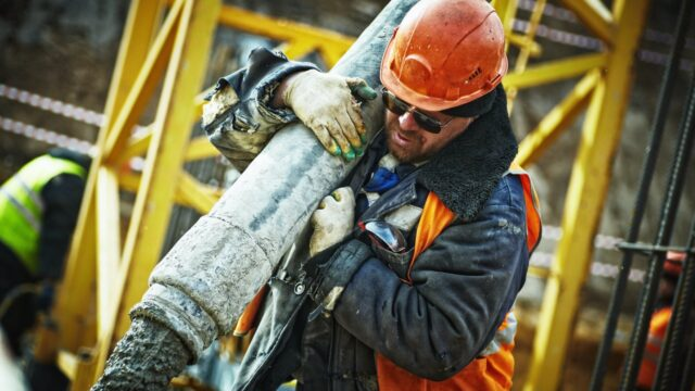 A construction worker carries a heavy pipe