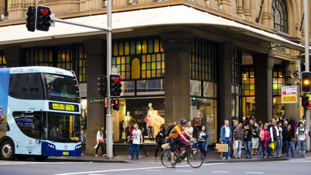 Busy city corner with bike and bus